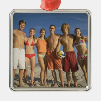 Friends posing on beach with volleyballs ornament