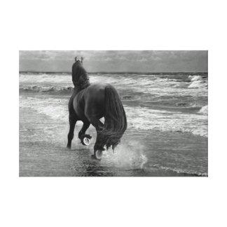 Friesian running on the beach canvas print