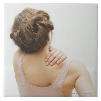 Frotamiento de la mujer que duele detrás azulejo cuadrado grande