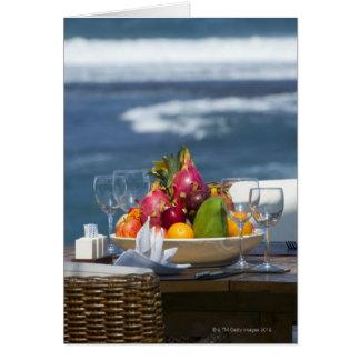 Frutas tropicales por el océano en la tabla tarjeta de felicitación
