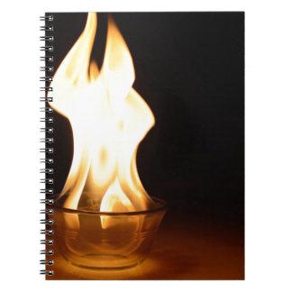 Fuego en un cuenco aislado en negro libros de apuntes con espiral
