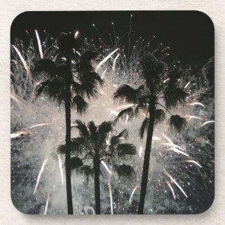 Fuegos artificiales detrás de las palmeras posavasos