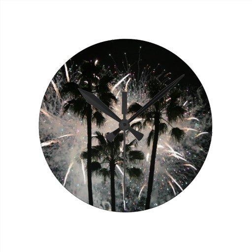 Fuegos artificiales detrás de las palmeras relojes de pared