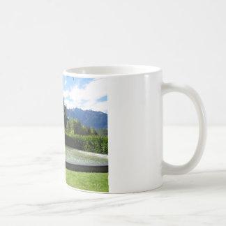 Fuente de agua con el fondo de la montaña taza básica blanca