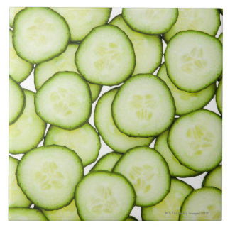 Full frame of sliced cucumber, on white ceramic tile