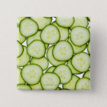 Full frame of sliced cucumber, on white pinback button