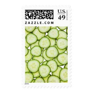 Full frame of sliced cucumber, on white stamps