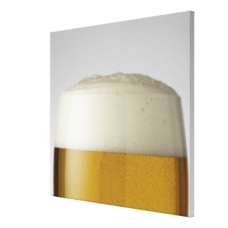 Full glass of beer indoors canvas print