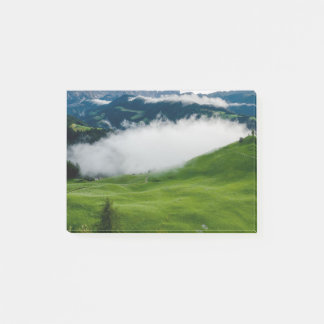 Full green mountain top with clouds beneath post-it notes