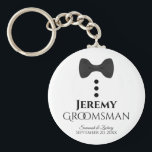 """Fun Black Tie Tuxedo Groomsman Wedding Favor Keychain<br><div class=""""desc"""">This cute keychain is designed as a gift for your groomsmen. Features a fun design with a black bow tie and buttons on a white background. The text reads """"Groomsman"""" with a place for his name, along with the names of the wedding couple & the date. Great way to thank...</div>"""