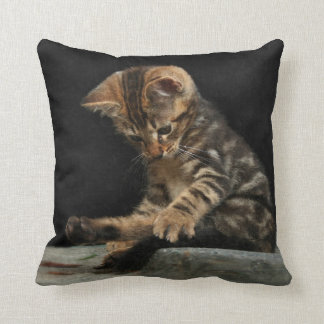 Funny kitten playing with tail throw pillow