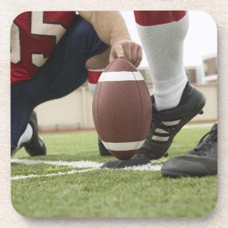 Fútbol de retroceso con el pie del futbolista posavasos de bebidas