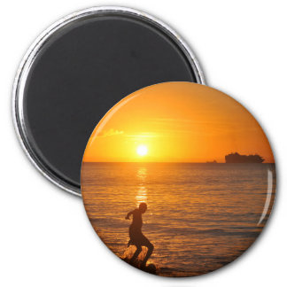 Fútbol en la puesta del sol imán redondo 5 cm