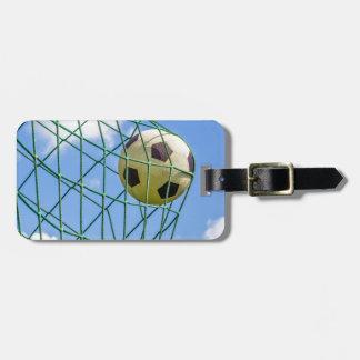 Fútbol tirado en red de la meta etiqueta de equipaje