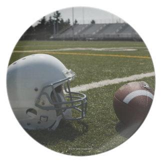 Fútbol y casco de fútbol americano en campo de plato de cena