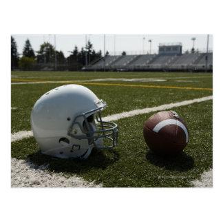 Fútbol y casco de fútbol americano en campo de postal