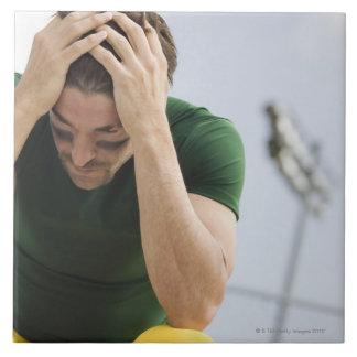 Futbolista derrotado con la cabeza en manos azulejo cuadrado grande