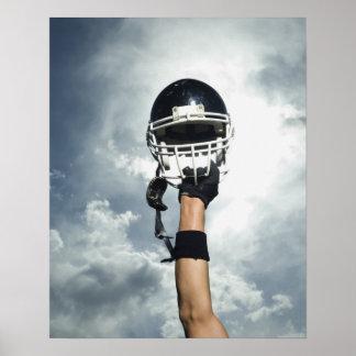Futbolista que celebra el casco en aire póster