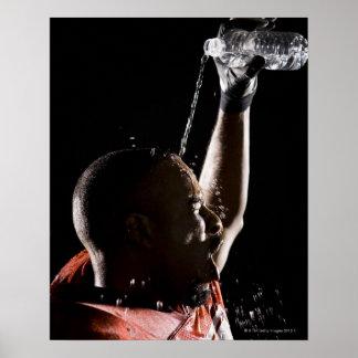 Futbolista que se refresca apagado con agua póster