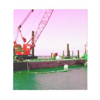 Gabarra flotante con la grúa verde y púrpura enton blocs de papel