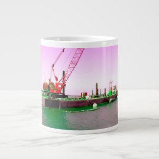 Gabarra flotante con la grúa verde y púrpura enton taza de café gigante