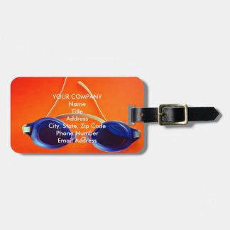 Gafas azules de la natación en el naranja etiquetas maleta