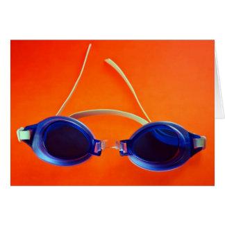 Gafas azules de la natación en el naranja tarjeton