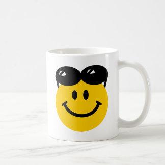 Gafas de sol encaramadas encima de la cara sonrien taza de café