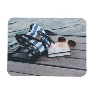 Gafas de sol, libro, monedero en muelle por el iman rectangular