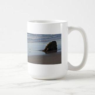 Gaitero de la arena en la playa taza