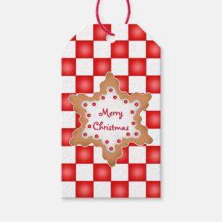 Galleta del navidad en el tablero de damas rojo y etiquetas para regalos