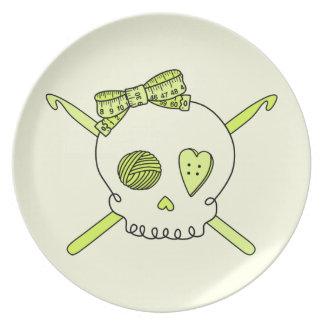 Ganchos del cráneo y de ganchillo (fondo amarillo) platos