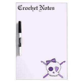 Ganchos del cráneo y de ganchillo fondo púrpura tableros blancos