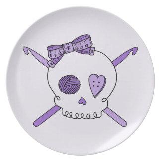 Ganchos del cráneo y de ganchillo (fondo púrpura) plato de cena