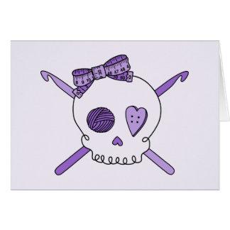Ganchos del cráneo y de ganchillo fondo púrpura tarjeta