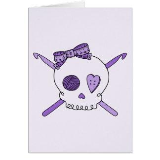 Ganchos del cráneo y de ganchillo fondo púrpura felicitaciones