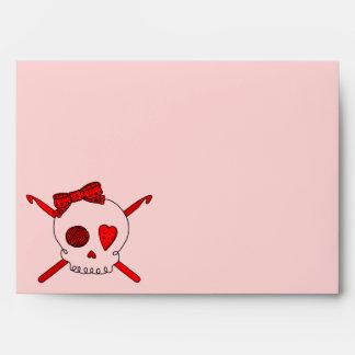 Ganchos del cráneo y de ganchillo (fondo rojo) sobres