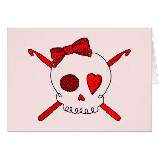 Ganchos del cráneo y de ganchillo fondo rojo tarjeta