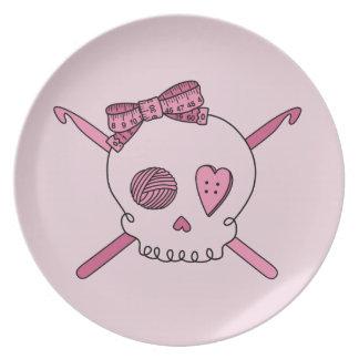 Ganchos del cráneo y de ganchillo (fondo rosado) plato de cena