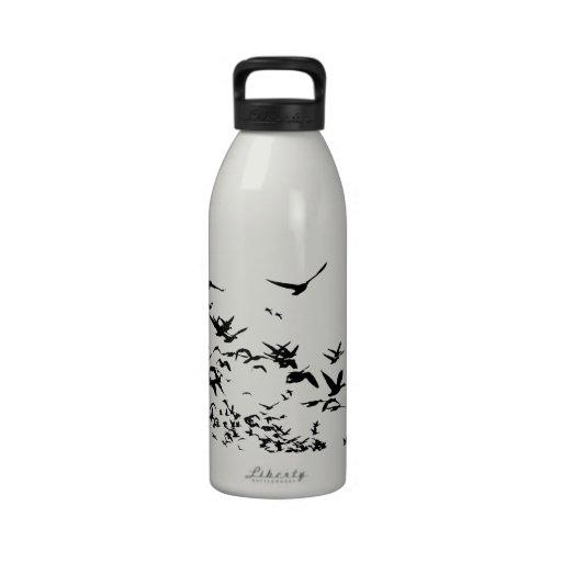 Gansos de nieve que emigran la botella de consumic botella de beber