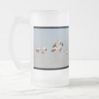 Gansos de nieve que vuelan la taza