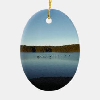 Gansos que vuelan sobre la reflexión de la montaña adorno navideño ovalado de cerámica
