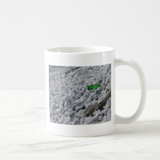 Garbage on the beach .Particular of a green bottle Coffee Mug