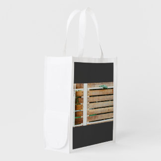 Garden guarded by wooden fence grocery bags