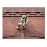 Gargoyle que cuelga en la pared de ladrillo roja postal