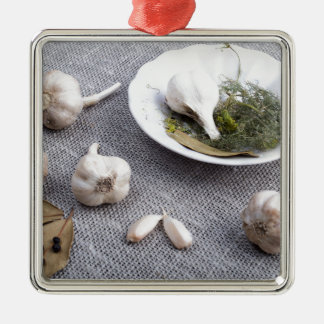 Garlic and spices on a gray fabric background metal ornament