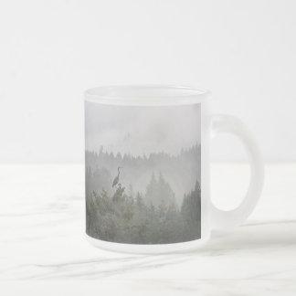 Garza en un paisaje de la montaña brumosa tazas