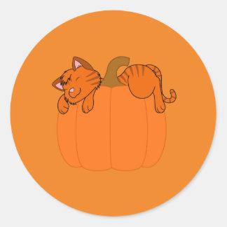 Gatito anaranjado que duerme en la calabaza de pegatina redonda
