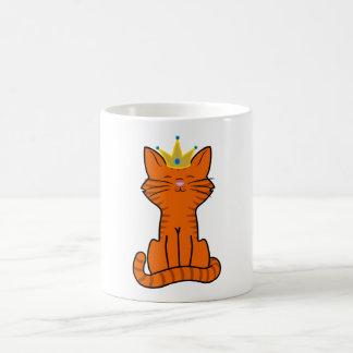 Gatito anaranjado que se sienta con la corona del taza