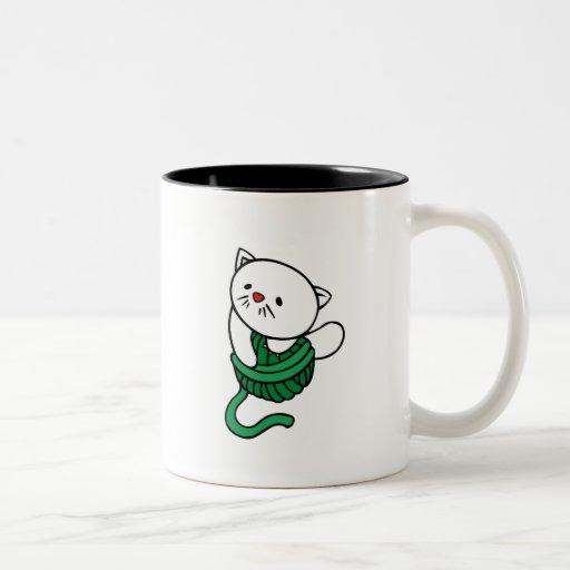 Gatito blanco con la bola del hilado tazas de café